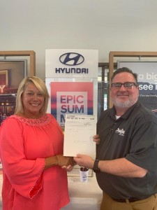 Mrs. Woods receiving a check from Hyundai representative.
